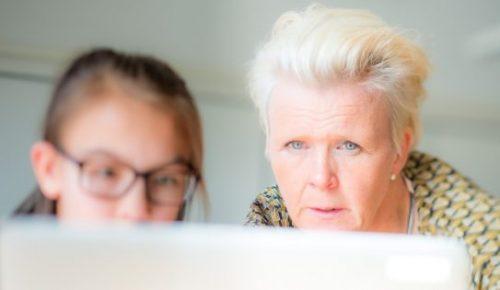 Lärare hjälper elev vid dator.