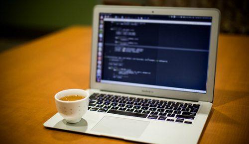 Macbook med kaffekopp på