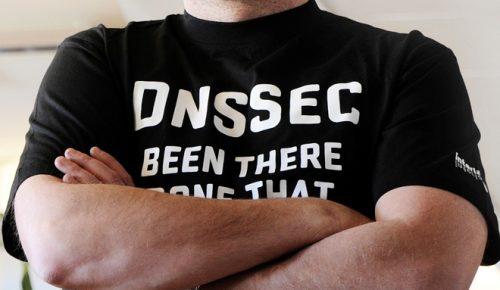 """Man står med armarna i kors och har en svart tröja med texten """"DNSSEC been there done that""""."""