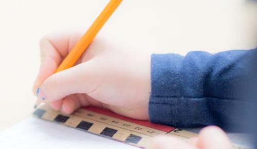 Barnhänder håller penna och linjal.