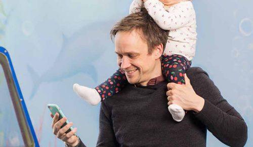 Bebis sitter på mans axlar som kollar på sin mobil.