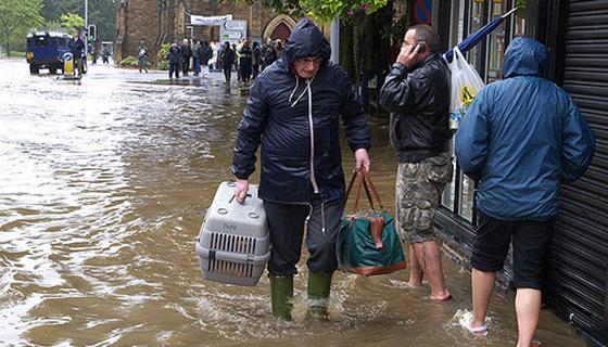 Äldre man i regnkläder och stövlar går med packning på översvämmad gata.