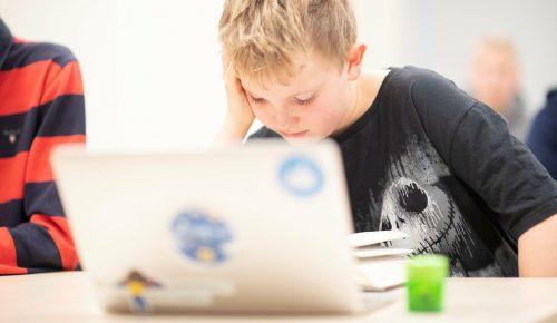 Pojke sitter framför en bärbar dator i ett klassrum.