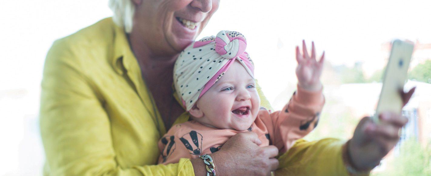 bebis och äldre kvinna ler mot mobil