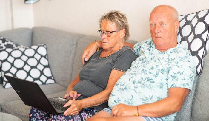 Äldre par sitter i soffan med en laptop.