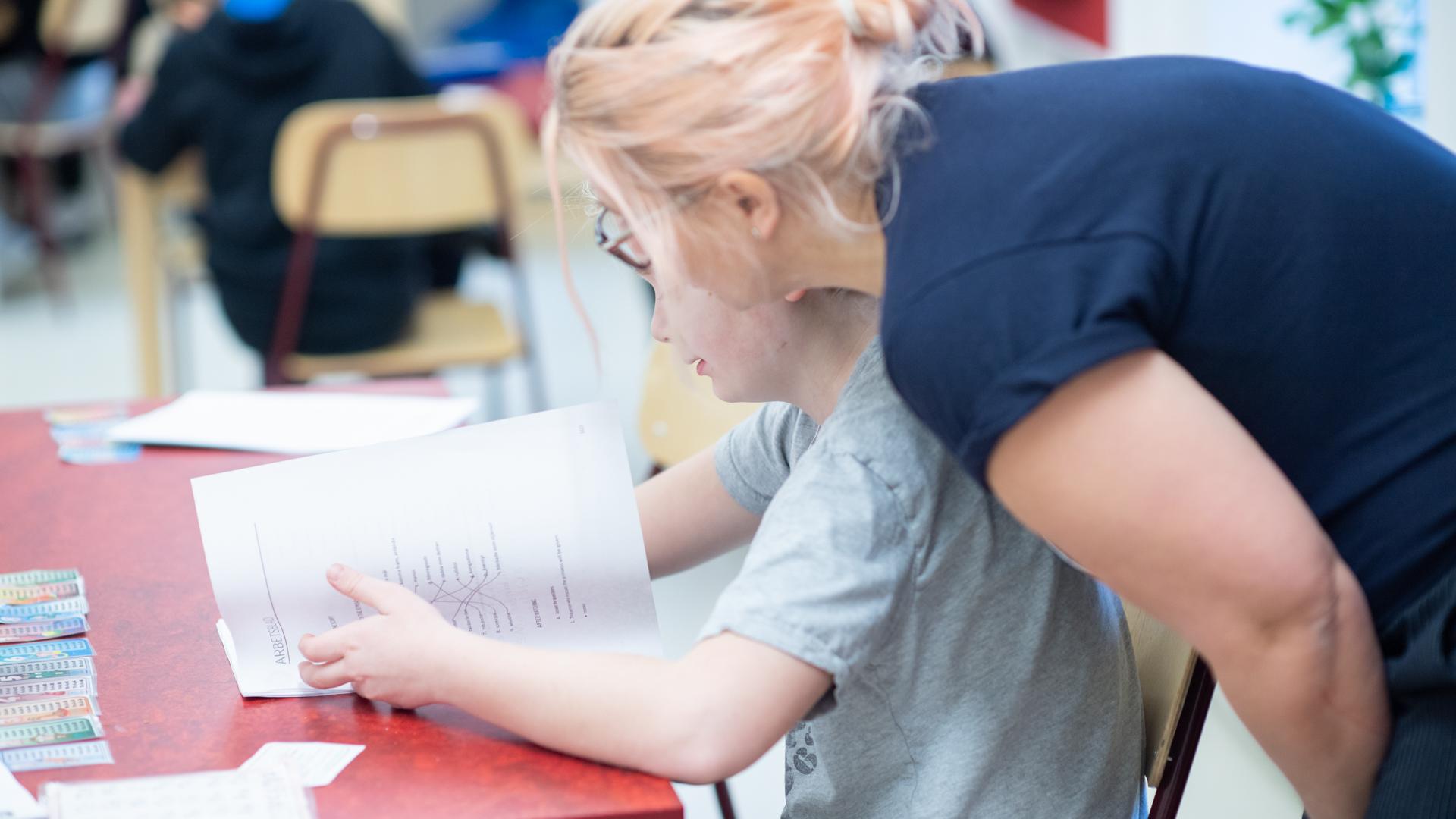 Lärare hjälper elev i klassrum.