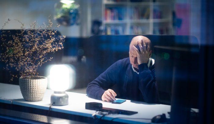 Man surfar på mobil med armbågen på bordet och huvudet lutande mot handen.