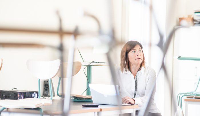 Kvinna sitter vid dator i ett klassrum.