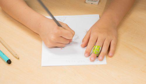 Barnhand med blåster ritar.
