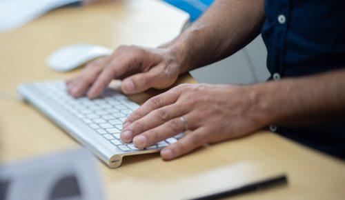 Händer skriver på ett tangentbord.
