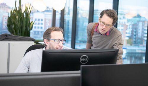 Två män tittar på en datorskärm på kontor.