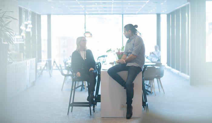 Man och kvinna konverserar på arbetsplats.