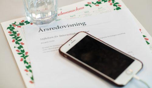 mobil ligger och laddar på årsredovisningspapper.