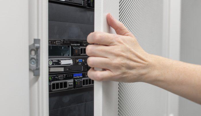 En hand öppnar en serverdörr