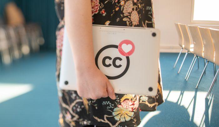 Kvinna bär en laptop med cc-klistermärke