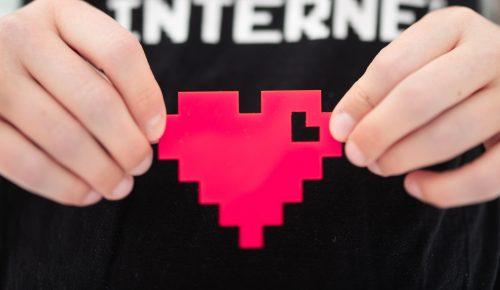 Händer håller upp pixelhjärta.