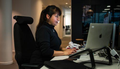 Kvinna sitter vid skrivbord med dator.