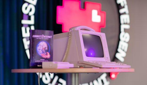 Gammal dator och modem framför skylt med Internetstiftelsens logotyp.