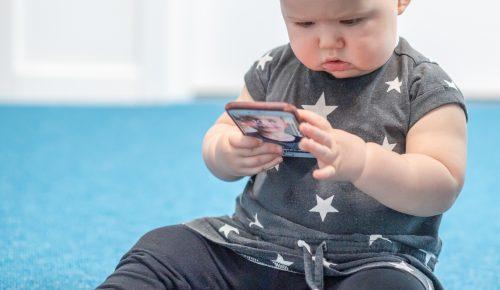 Bebis tittar på en mobiltelefon i handen.