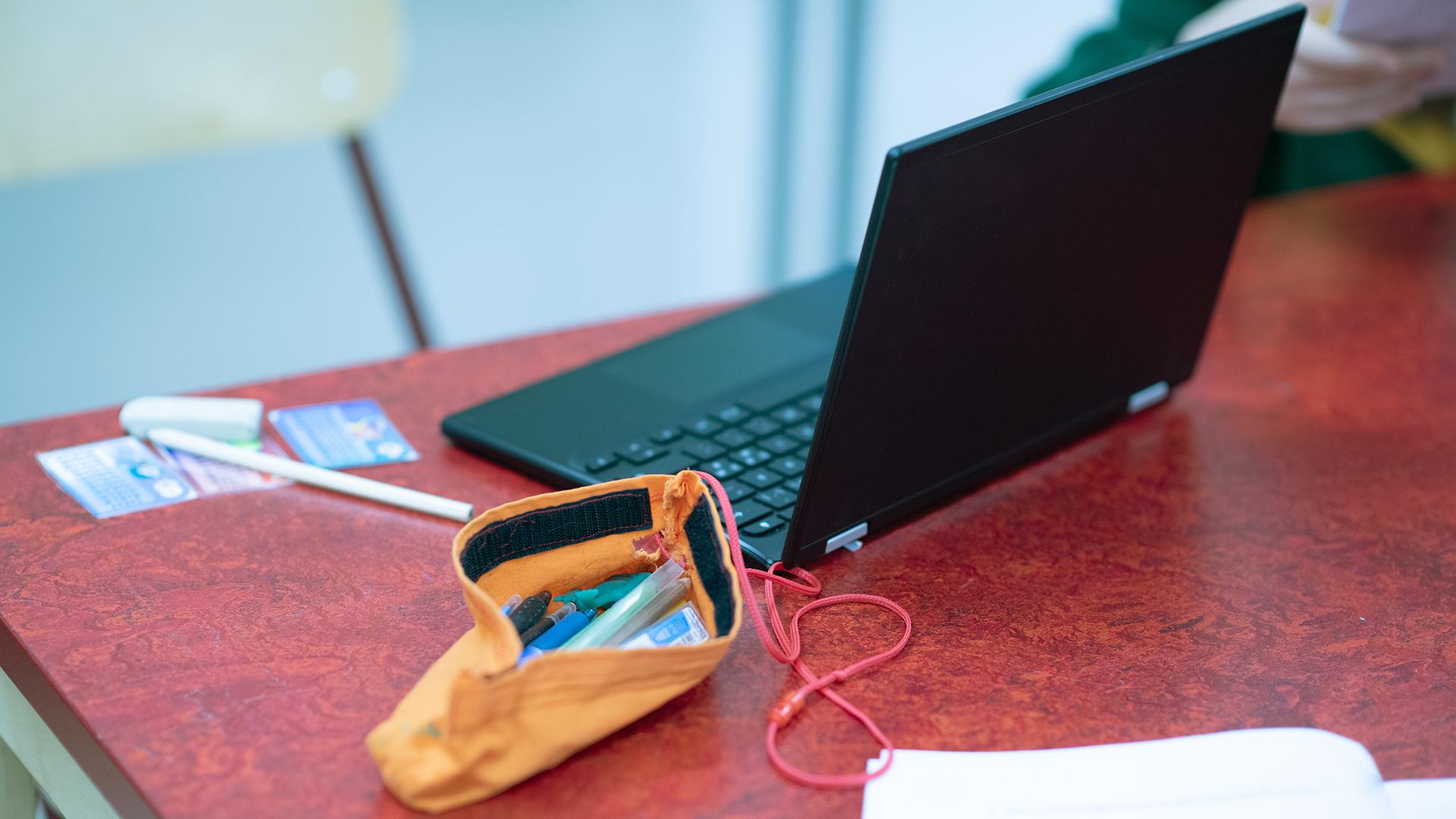 Dator och pennskrin på bord.