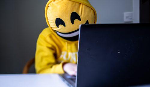 Person med emojikudde framför ansiktet sitter vid dator.
