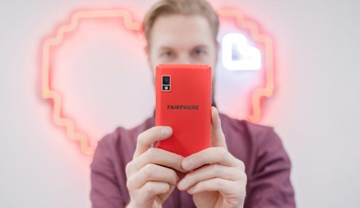 Man håller upp en röd fairphone.