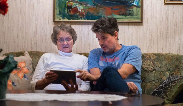 Man hjälper äldre kvinna med surfplatta i soffan.
