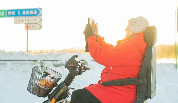 Äldre kvinna i elscooter tar bild med mobil.