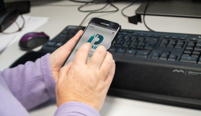 Händer håller mobil med mobilt bank-ID.