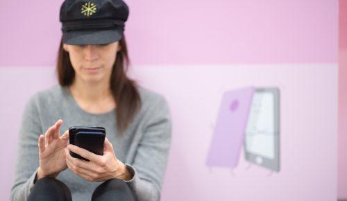 kvinna sitter med mobil.