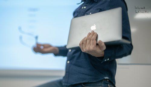 Man håller laptop framför whiteboard.