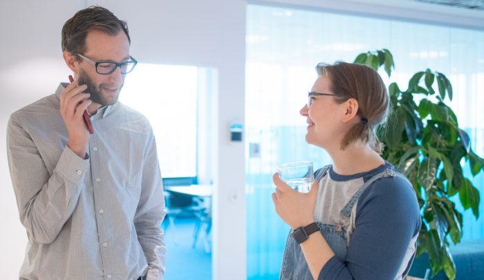 Man och kvinna konverserar i arbetsmiljö.