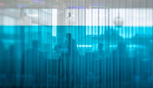 Medarbetare bakom blå gardiner.