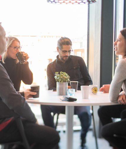 Grupp medarbetare på internetstiftelsen konverserar vid bord.