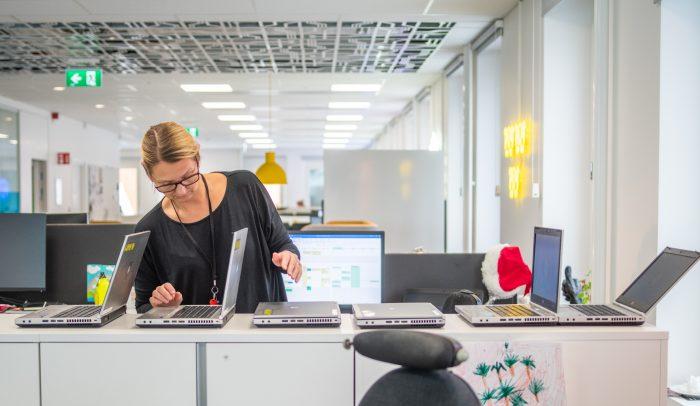 Kvinna inspekterar datorer i kontorsmiljö.