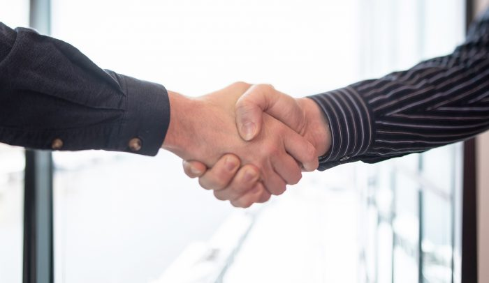 Ett handslag mellan två personer