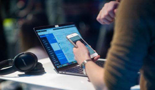 Person sitter vid bord med dator och mobiltelefon.