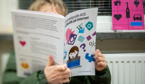 Ett barn sitter och bläddrar i Internetstiftelsens internetguide Källkritik på internet