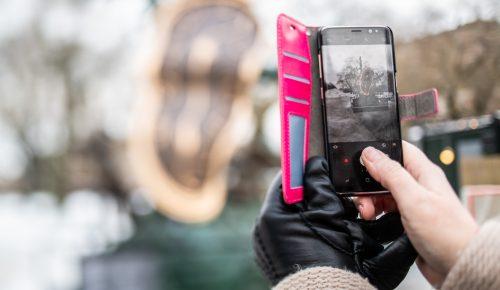 Händer tar foto med en mobil utomhus.
