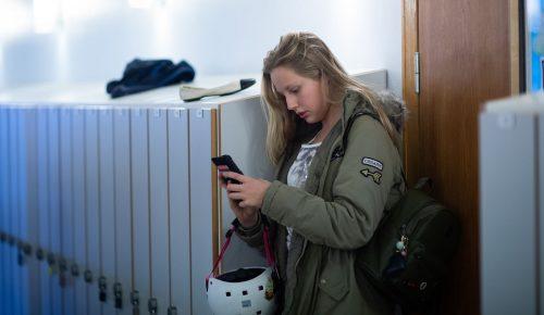 Ung tjej använder en mobiltelefon bland skåp.