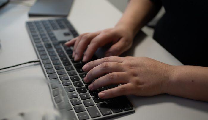 Händer som skriver på ett tangentbord.
