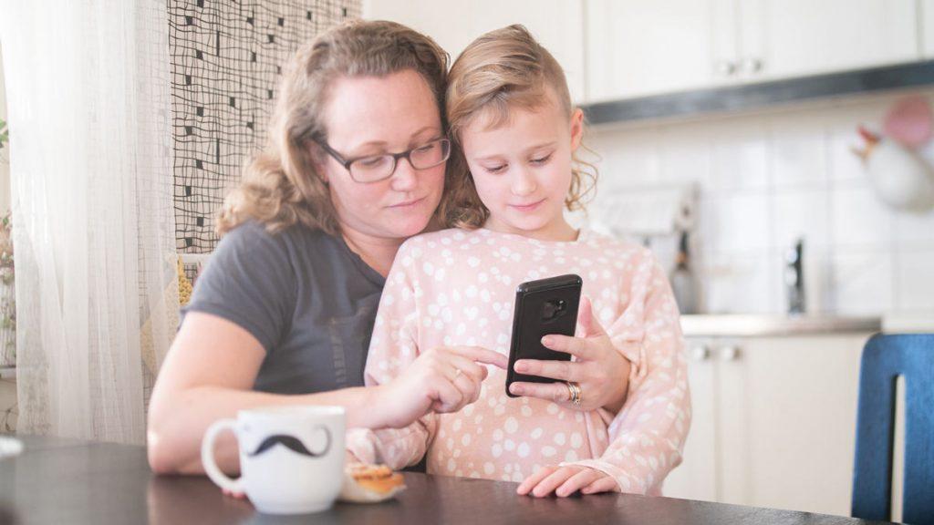 Förälder och barn tittar på mobiltelefon.