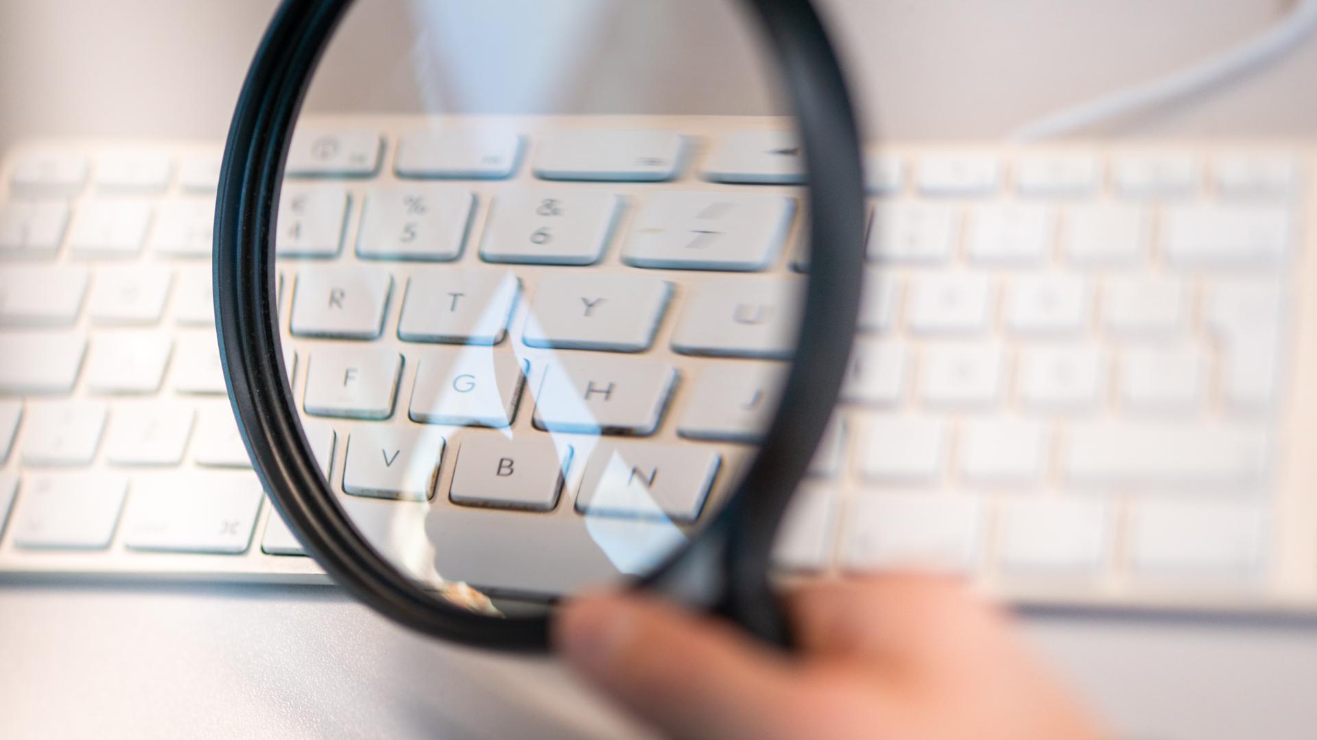 Någon tittar på ett tangentbord genom ett förstoringsglas.