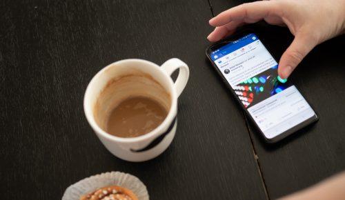 Mobiltelefon med en hand som surfar på Facebook.