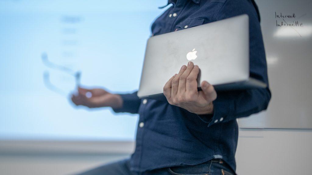 Person med bärbar dator i handen.
