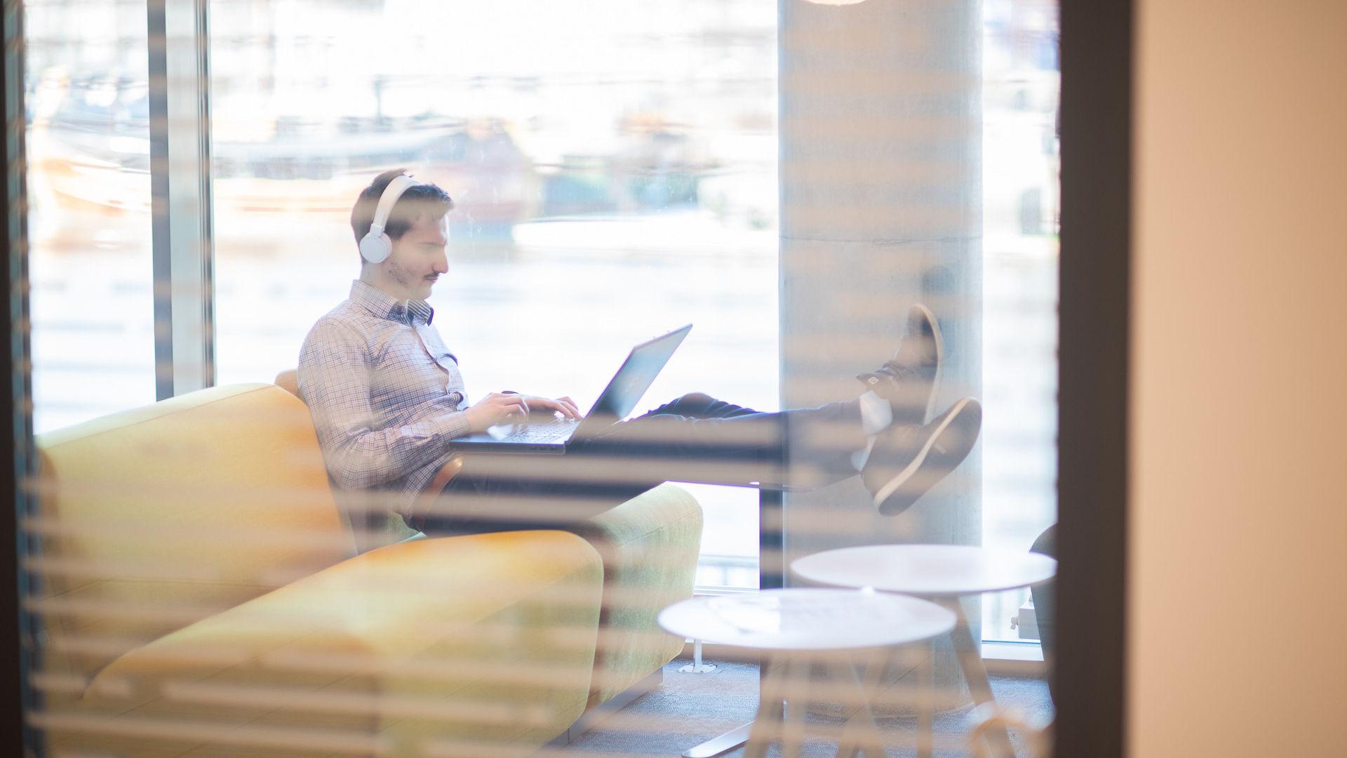 Man sitter i soffa med en laptop i knät och hörlurar på huvudet.