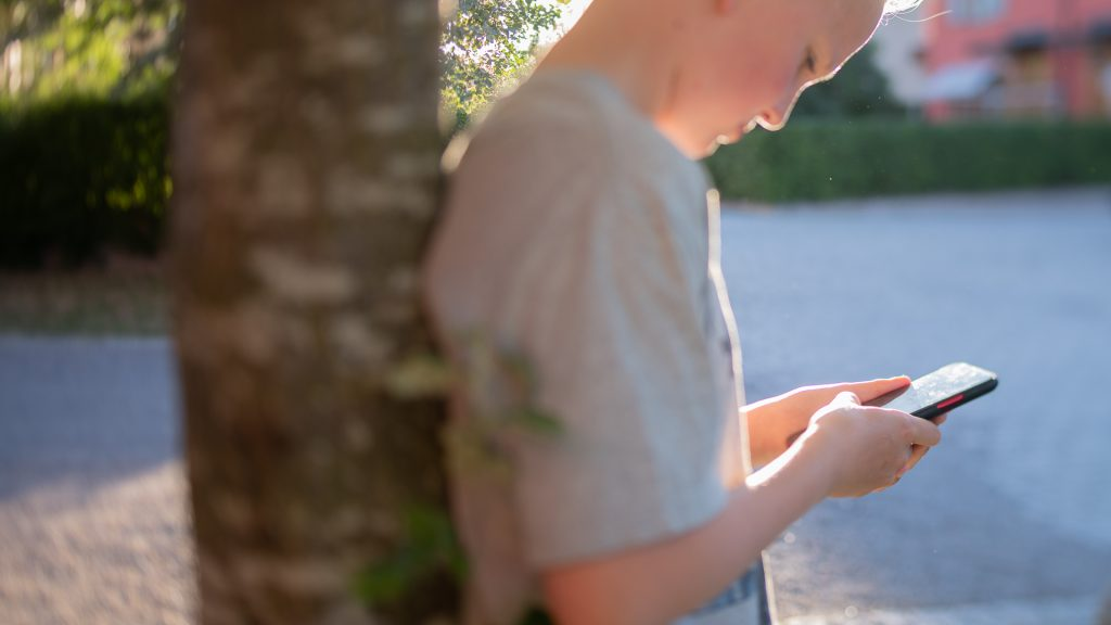 Barn som använder mobiltelefon.