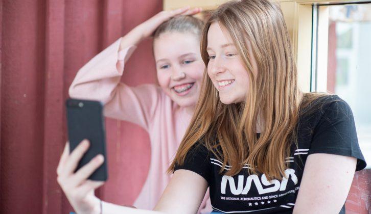 två elever med mobiltelefon.