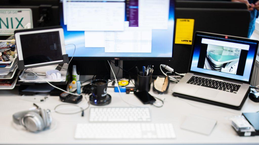 Skrivbord med dator, mobiltelefon och surfplatta.
