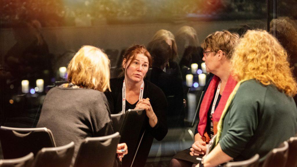 Fyra personer som sitter och diskuterar i grupp.